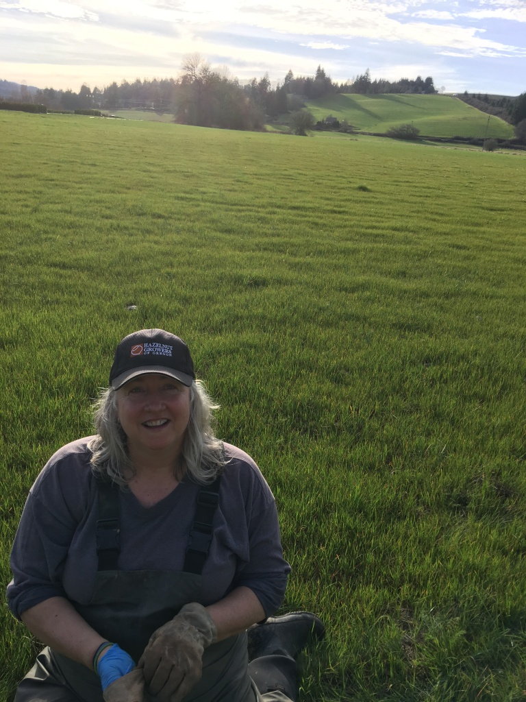 Debbie sitting in the field getting ready to plant Red Alders in March 2017.